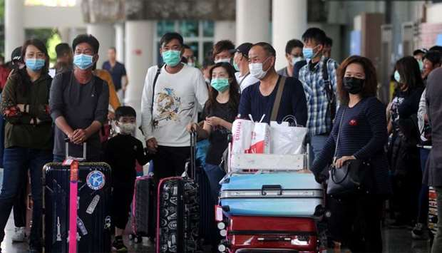 Passengers wearing medical masks walk at the international arrivals terminal