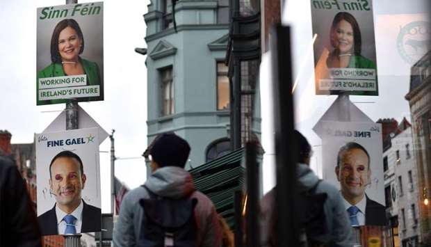 Pedestrians walk past campaign posters featuring Sinn Fein President Mary Lou McDonald and also Irel