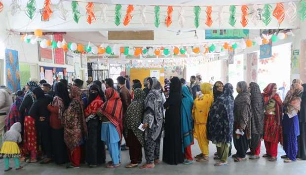 Voters stand in queues as they wait to cast their vote outside a polling booth during the state asse