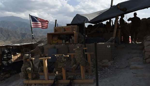 US Army soldiers from NATO look on as US flag flies at a checkpoint during a patrol at the Deh Bala