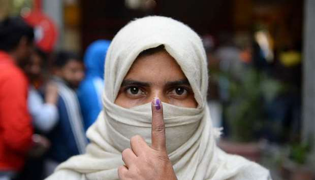 A woman shows her ink-marked finger after casting her vote at a polling station during the Legislati