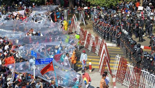 People cover with plastic in case of a water canon use during a rally against the military coup and