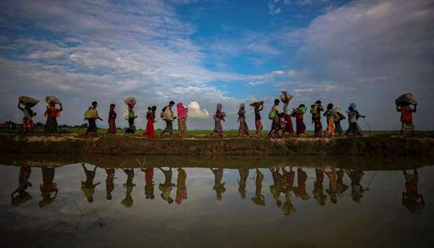 Rohingya refugees are reflected in rain water along an embankment next to paddy fields after fleeing