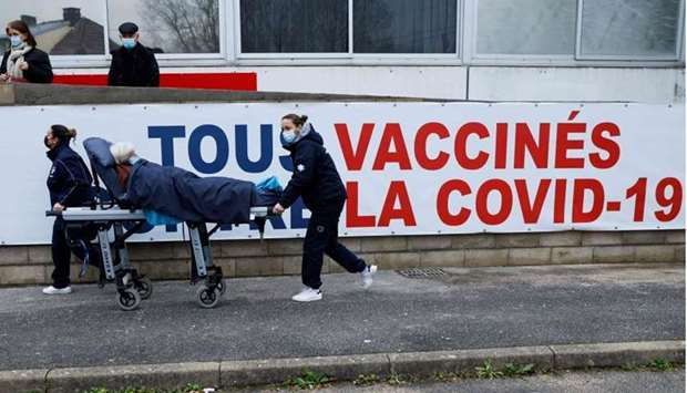 A woman is carried on a stretcher to the Covid-19 vaccination center at the South Ile-de-France Hosp