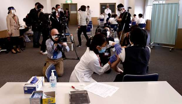 Members of the media look on as a medical worker (R) receives a dose of the coronavirus disease (Cov