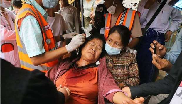 A protester has a wound on her head treated after being beaten by security forces during a demonstra