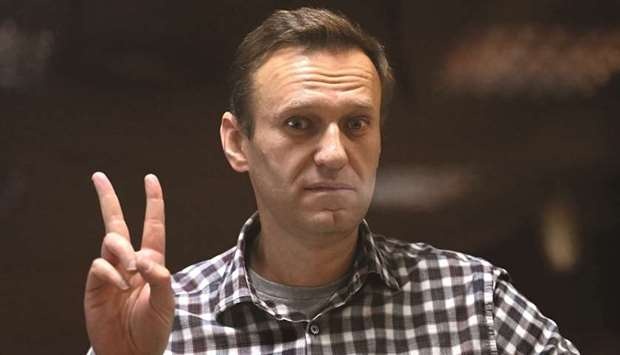 Navalny gestures from inside a glass cell during a court hearing at Moscow's Babushkinsky district c