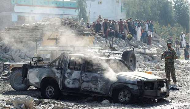 An Afghan National Army soldier inspects the wreckage of a burnt army car at the site of a blast in