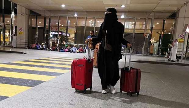 A Saudi woman walks with her luggage as she arrives at King Fahd International Airport in Dammam, Sa