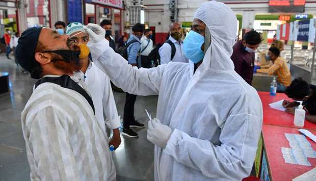 A health worker wearing protective gear takes a nasal swab sample of arriving passengers for conduct