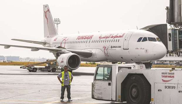 A worker of Tunis-Carthage International Airport stands near a TunisAir Airbus A320 aircraft on the