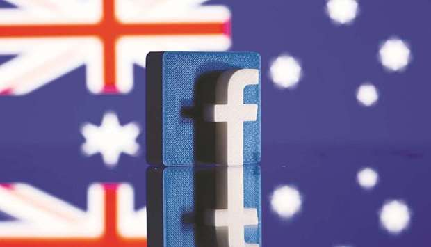 A 3D-printed Facebook logo is seen in front of a displayed Australian flag in an illustration pictur