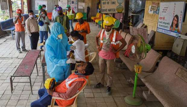 A health worker wearing protective gear takes a swab sample of a labourer for a Covid-19 coronavirus