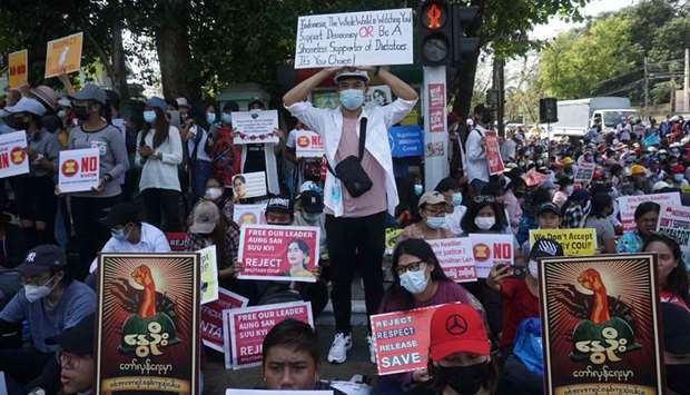 Protesters hold signs as they take part in a demonstration against the military coup in Yangon