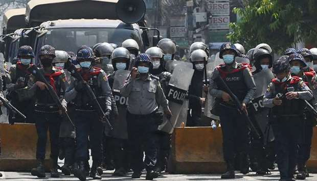 Riot police march on a road to clear away protesters from holding a demonstration against the milita