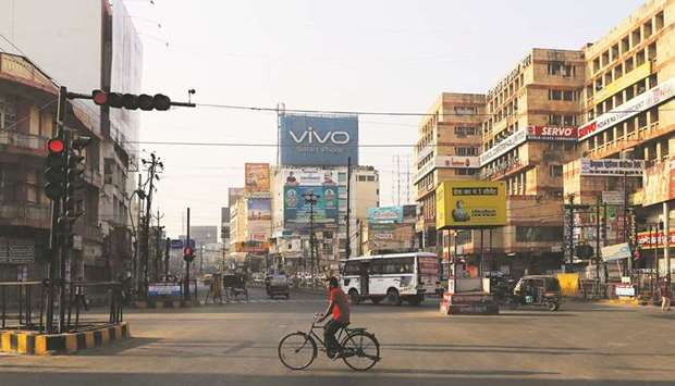 A cyclist rides through a junction in Patna, India. Gross domestic product expanded 0.4% in the thre