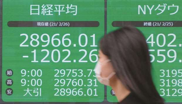 A pedestrian walks past an electronic quotation board displaying share prices in Tokyo. The Nikkei 2