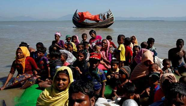 (file photo) Rohingya refugees sit on a makeshift boat after crossing the Bangladesh-Myanmar border,