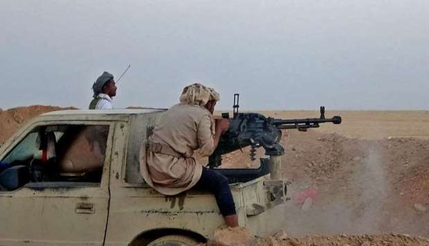 A combatant mans a heavy machine gun as forces loyal to Yemen's government clash with Houthi fighter