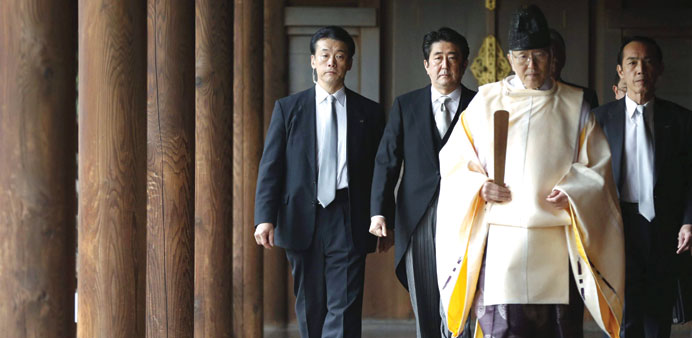 Japan's Prime Minister Shinzo Abe  being led by a Shinto priest as he visits Yasukuni shrine in Toky