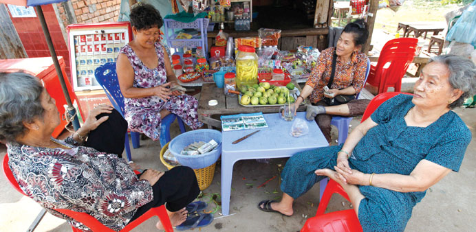 Vietnamese women sit at a shop in their community in Phnom Penh, Cambodia.
