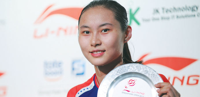 China's Wang Yihan poses with the plaque after defeating compatriot Li Xuerui in the women's singles