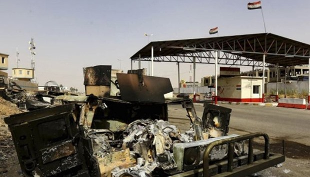 Burnt vehicles belonging to Iraqi security forces are pictured at a checkpoint