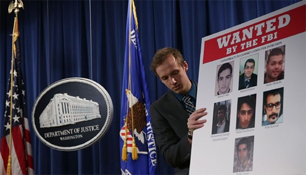 A Department of Justice employee put up a poster of the seven indicted hackers