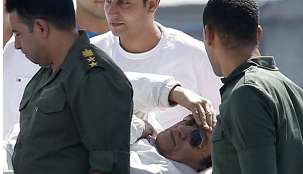 Egypt's former president Hosni Mubarak touches his head as he is transported back to a military hosp