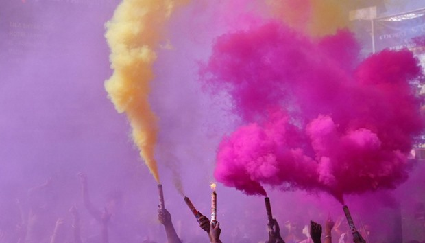 People release coloured smoke as they take part in Holi