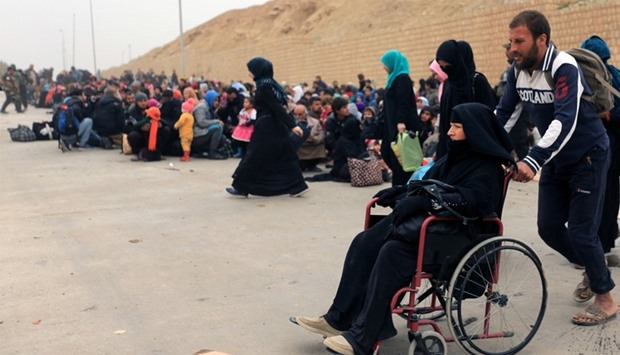 Displaced Iraqi people who have fled their homes because of the clashes, wait to be taken to safe pl