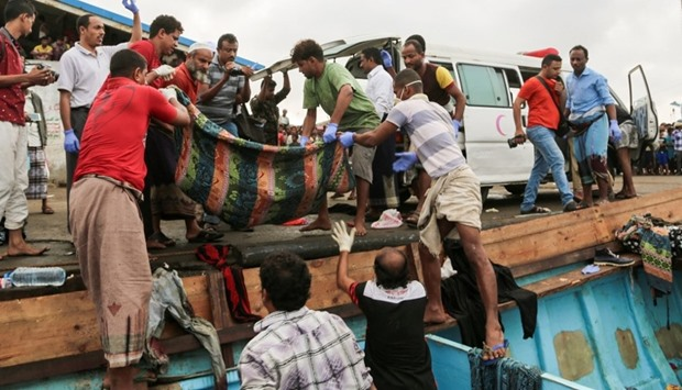 Yemeni officers carry the bodies of Somali refugees, killed in attack