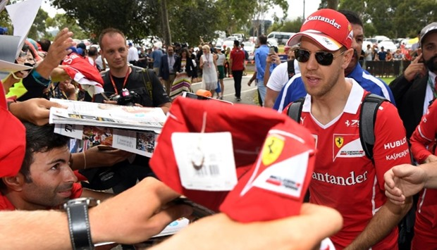 Ferrari's German driver Sebastian Vettel signs autographs for fans before the Formula One Australian