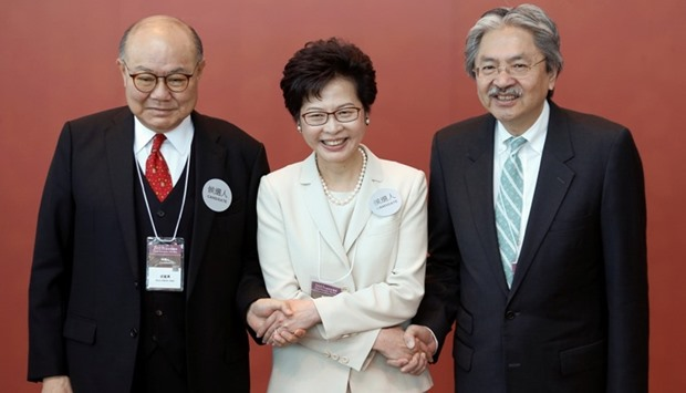 Carrie Lam (C) poses with Woo Kwok-Hing (L) and John Tsang (R) as they greet election committee memb