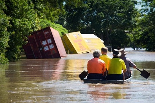 A group of workers paddle in a small boat to check on a flooded house in Beenleigh, Queensland