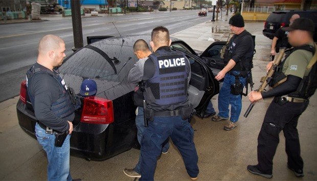 US Immigration and Customs Enforcement officers detain an unauthorized migrant