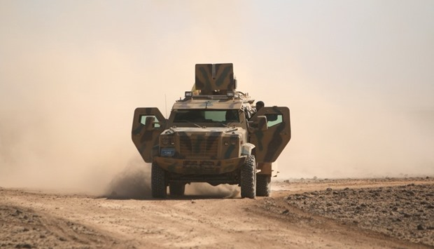 Syrian Democratic Forces(SDF) fighters ride a military vehicle north of Raqqa city