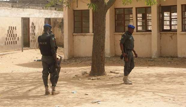 Policemen stand on guard at the premises of Government Girls Technical College at Dapchi town in nor