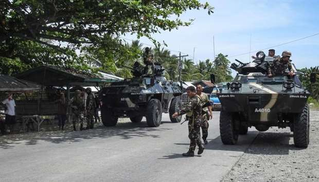 Philippine soldiers standing next to their armoured personnel carriers as they man a checkpoint alon