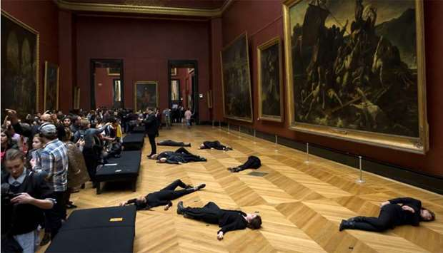 Members of the environmental activist group '350.org' lie on the floor in front of Theodore Gericaul