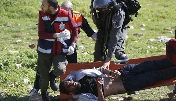 An Israeli soldier attempts to detain an injured Palestinian demonstrator as he's carried on a stret