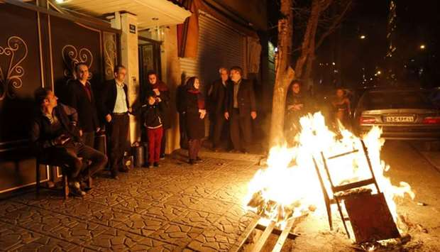 Iranian families light fire outside their houses in Tehran on March 13, 2018 during the Wednesday Fi