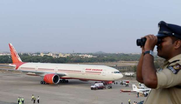 An Indian policeman watches over Begumpet Airport as an Air India Boeing 777 sits on the tarmac