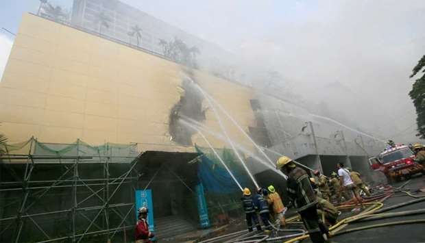 Firefighters douse water after a fire engulfed the Manila Pavilon hotel in Metro Manila