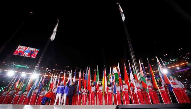 National flags of participating countries are carried into the stadium