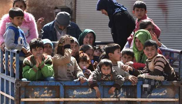 Civilians, fleeing the city of Afrin in northern Syria, are seen arriving in the village of az-Ziyar