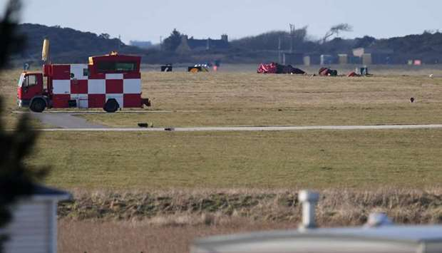 Debris from a crashed Royal Air Force (RAF) jet lays on the grass close to the runway at RAF Valley,