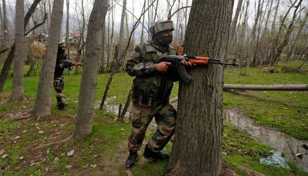 Indian Army soldiers take their positions near the site of a gunbattle on the outskirts of Srinagar.