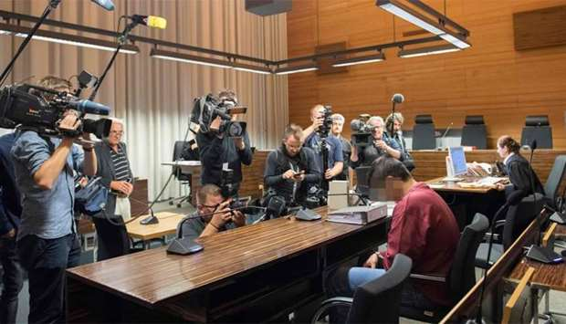 Photographers and cameramen take pictures of Hussein Khavari, who is accused of raping and killing a