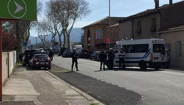 Police are seen at the scene of a hostage situation in a supermarket in Trebes, Aude.